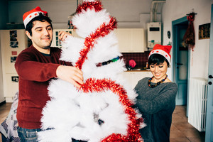 Half length of couple of young handsome caucasian man and woman decorating christmas tree having fun - christmas, holiday, winter concept