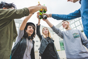 Half length of group of young handsome multiethnic woman and man friends making a toast with beers, having fun together - celebrating, happiness, friendship concept