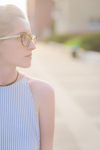 Half length of the profile of a young handsome caucasian blonde italian designer, overlooking left, wearing striped shirt and speckled glasses - youth, pensive, serious concept - backlight
