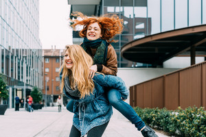 Half length of two blonde and redhead women friends having fun outdoor in the city, riding piggyback - happiness, friendship, having fun concept