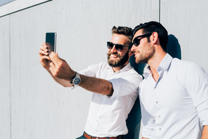 Half length of two young bearded blonde and black hair modern businessman, leaning against a wall, using smartphone, taking a selfie - technology, vanity, social network concept