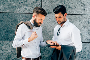 Half length of two young bearded blonde and black hair modern businessman, leaning against a wall, using tablet, looking downward the screen - technology, business, work concept