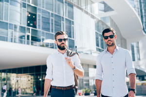 Half length of two young bearded blonde and black hair modern businessman, walking in the city backlight, one looking in camera, the other overlooking right - working, successful concept