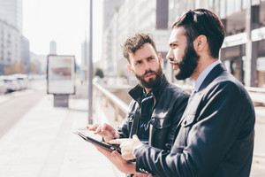 Half length of two young bearded modern businessman using tablet handhold looking downward the screen - technology, business, work concept
