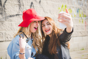 Half length of two young beautiful blonde and brunette girls having fun in the city taking selfie with smartphone - technology, vanity, social network, communication concept