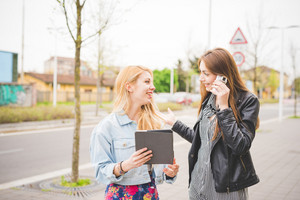 Half length of two young blonde and brunette girls walking through the city using a tablet - technology, communication, social network concept