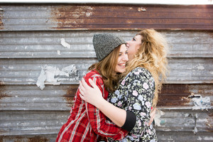 Half length of two young curly and straight blonde hair caucasian woman hugging, smiling and having fun together - carefreeness, youthful, friendship, concept