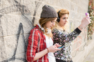 Half length of two young curly and straight blonde hair caucasian woman leaning against a wall, both listening music and using a smartphone handheld, focus on the one in foreground - technology, music, communication concept