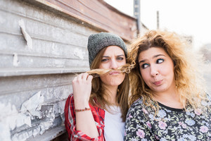 Half length of two young curly and straight blonde hair caucasian woman leaning on a wall, one playing with the other's hair, use it in shape of mustache - youthful, carefreeness, friendship concept