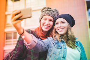 Half length of two young handsome caucasian blonde and redhead hair women hugging outdoor in the city, holding smartphone, taking selfie, smiling - social network, communication, vanity concept - colorful filtered