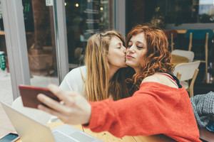 Half length of two young handsome caucasian blonde and redhead hair women outdoor in the city, holding smartphone, taking selfie, kissing on the cheek- social network, communication, vanity concept