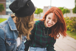 Half length of two young handsome caucasian women friends chatting, focus on the redhead laughing - smiling, friendship, having fun concept