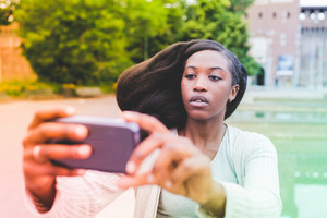 Half length of young beautiful afro black woman outdoor in the city holding a smart phone taking selfie - technology, vanity, social network concept