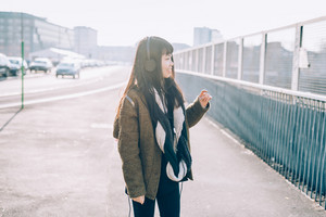 Half length of young beautiful asian hipster woman in the city back light listening music with headphones, smiling - music, technology, relax concept