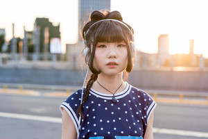Half length of young beautiful asian millennial woman nonconformist listening music with headphone outdoor in the city back light, looking at camera - serious, music, relax concept