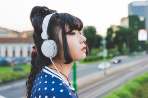 Half length of young beautiful asian millennial woman nonconformist listening music with headphone outdoor in the city back light, overlooking thinking future, serious, music, relax concept