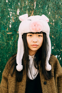 Half length of young beautiful asiatic hipster woman in the city serious looking in camera - wearing funny piggy winter cap
