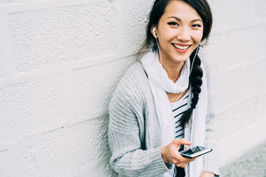Half length of young beautiful asiatic woman holding a smart phone listening music with earphones, looking in camera, smiling - technology, happiness, music concept