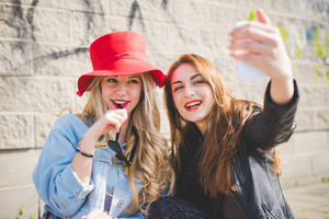 Half length of young beautiful blonde and brunette multiethnic girls having fun in the city taking selfie with smartphone - technology, vanity, social network concept