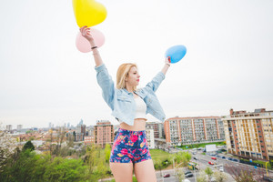 Half length of young beautiful blonde caucasian girl playing with colorful balloons in the suburbs - childhood, carefree, valentine concept