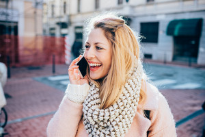 Half length of young beautiful blonde caucasian woman outdoor in the city talking smart phone, laughing - communication, technology, conversation concept