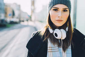 Half length of young beautiful blonde straight hair woman in the city with headphones listening to music, looking in camera serious - happiness, relaxing, technology concept