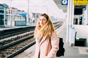 Half length of young beautiful caucasian blonde woman at the train station waiting for train overlooking pensive - commuter, transport, serious concept