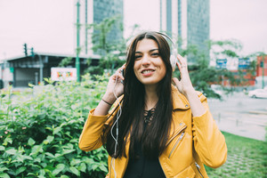 Half length of young beautiful caucasian brown long hai woman listening music with headphones looking at camera smiling - relax, fun, happiness concept