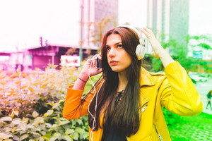 Half length of young beautiful caucasian brown long hair woman listening music with headphones outdoor in the city- relax, fun, happiness concept