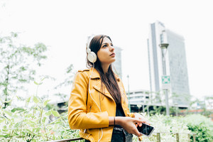 Half length of young beautiful caucasian brown long hair woman listening music with headphones outdoor in the city using smart phone - relax, fun, happiness concept