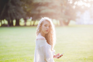 Half length of young beautiful caucasian long curly blonde hair woman outdoor in a city park in back light holding smart phone looking at camera - technology, serenity, carefree concept