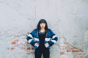 Half length of young beautiful eastern woman posing leaning against a wooden wall, looking over, serious - determination, girl power, pensive concept