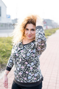 Half length of young curly blonde hair caucasian girl posing in the city street, touching her hair, looking in camera, smiling - youthful, carefreeness concept