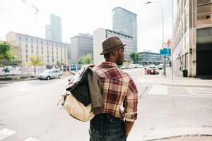 Half length of young handsome afro black man walking in the street of the city, holding a bag, overlooking right, backview, wearing jeans overalls and checked shirt