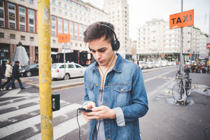 Half length of young handsome alternative dark model man in town listening to music with headphones and smartphone, looking downward - music, technology, relaxing concept