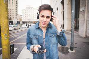 Half length of young handsome alternative dark model man in town listening to music with headphones and smartphone, looking in camera smiling - music, technology, relaxing concept