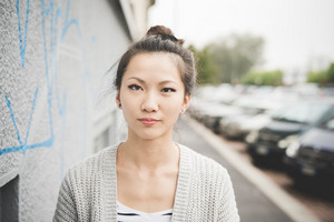 Half length of young handsome asiatic chinese woman with hair tied, looking in camera, thoughtful - thinking future, serious concept