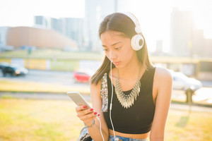 Half length of young handsome asiatic long brown straight hair woman listening music with headphone while using a smartphone, looking downward the screen - technology, music, relaxing concept