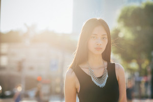 Half length of young handsome asiatic long brown straight hair woman posing in the city back light, looking in camera, smiling - serene, happiness, carefreeness concept