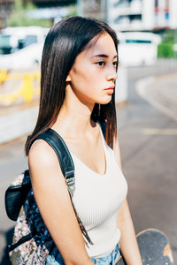 Half length of young handsome asiatic long brown straight hair woman posing in the city, looking in camera, holding a backpack, smiling - serene, happiness, carefreeness concept