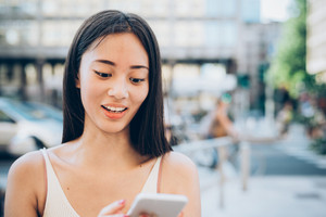 Half length of young handsome asiatic long hair woman in the city, holding smartphone looking downward and tapping the screen - internet, social network, technology concept