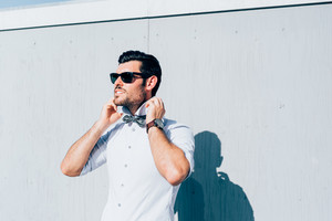 Half length of young handsome black hair caucasian modern businessman posing leaning against a wall, overlooking right, wearing bow tie - business, successful concept