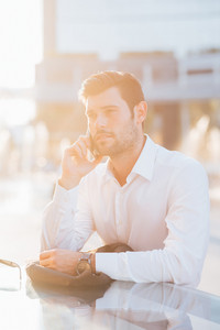 Half length of young handsome black hair caucasian modern businessman talking smartphone in city backlight- business, working, communication concept