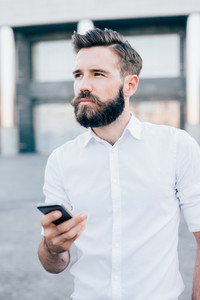 Half length of young handsome blonde caucasian modern businessman holding a smartphone, overlooking right, pensive - business, working, technology concept