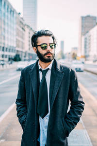 Half length of young handsome caucasian bearded businessman posing outdoor in the street, overlooking pensive wearing sunglasses - business, thoughtful, serious concept
