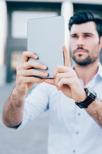 Half length of young handsome caucasian black hair modern businessman using a tablet taking photos - technology, social network concept - focus on the tablet