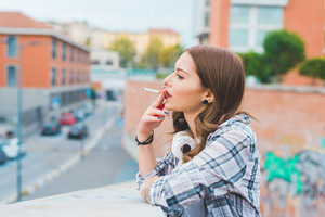 Half length of young handsome caucasian blonde straight hair woman leaning on a handrail, looking straight smoking a cigarette, serene, headphones around her neck - carefree, youth concept