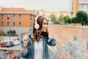 Half length of young handsome caucasian blonde straight hair woman listening music with headphones, looking over smiling - music, technology, relaxing concept