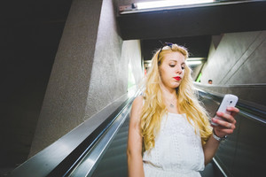 Half length of young handsome caucasian blonde straight hair woman on a escalator in the subway, holding a smartphone, looking downward and tapping the screen - technology, communication concept