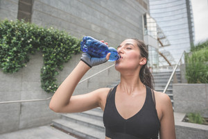 Half length of young handsome caucasian brown hair sportive woman drinking water from a bottle, having a break from training - relaxing, break, training concept